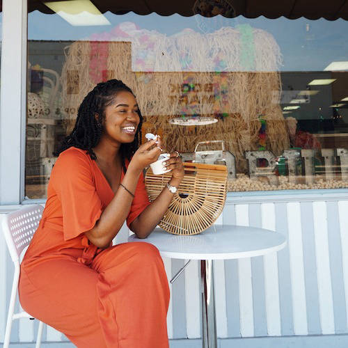 Woman eating ice cream at a table outside