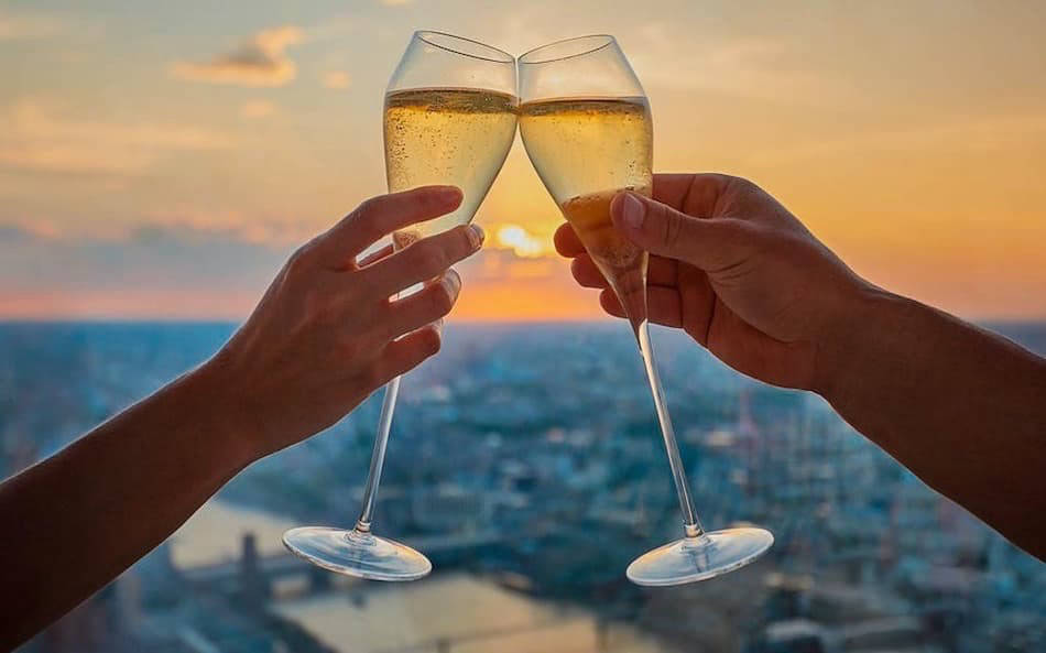 Two champagne glasses at sunset