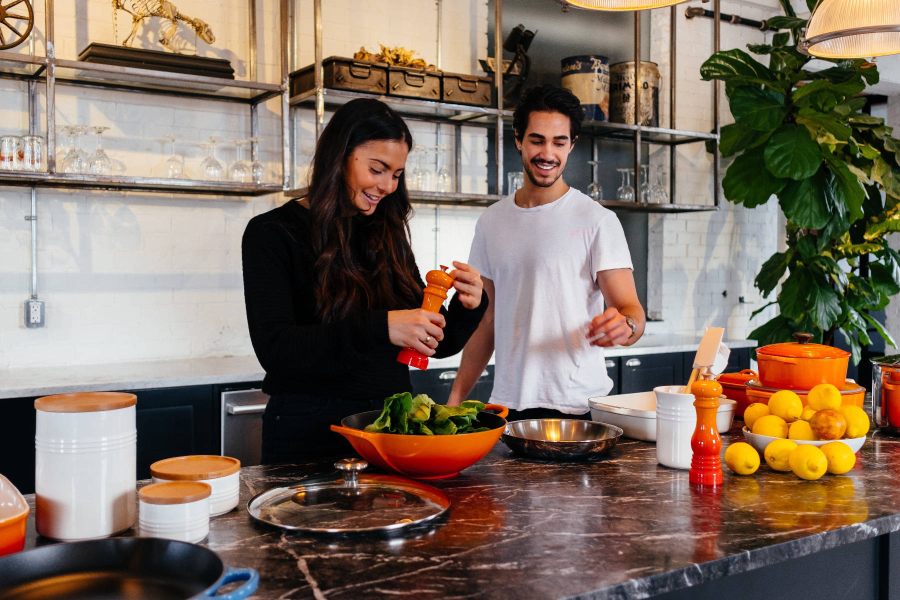 Couple making food in bright kitchen