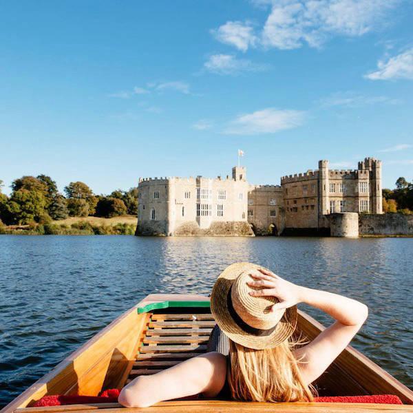 Woman in boat on lake overlooking castle