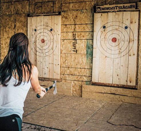Woman throwing an axe at a target