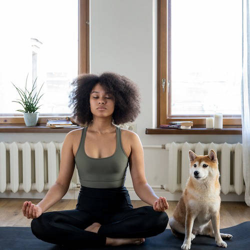 Woman doing meditation with her dog
