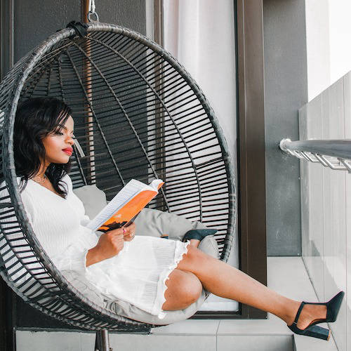 Woman reading a book in a hanging chair
