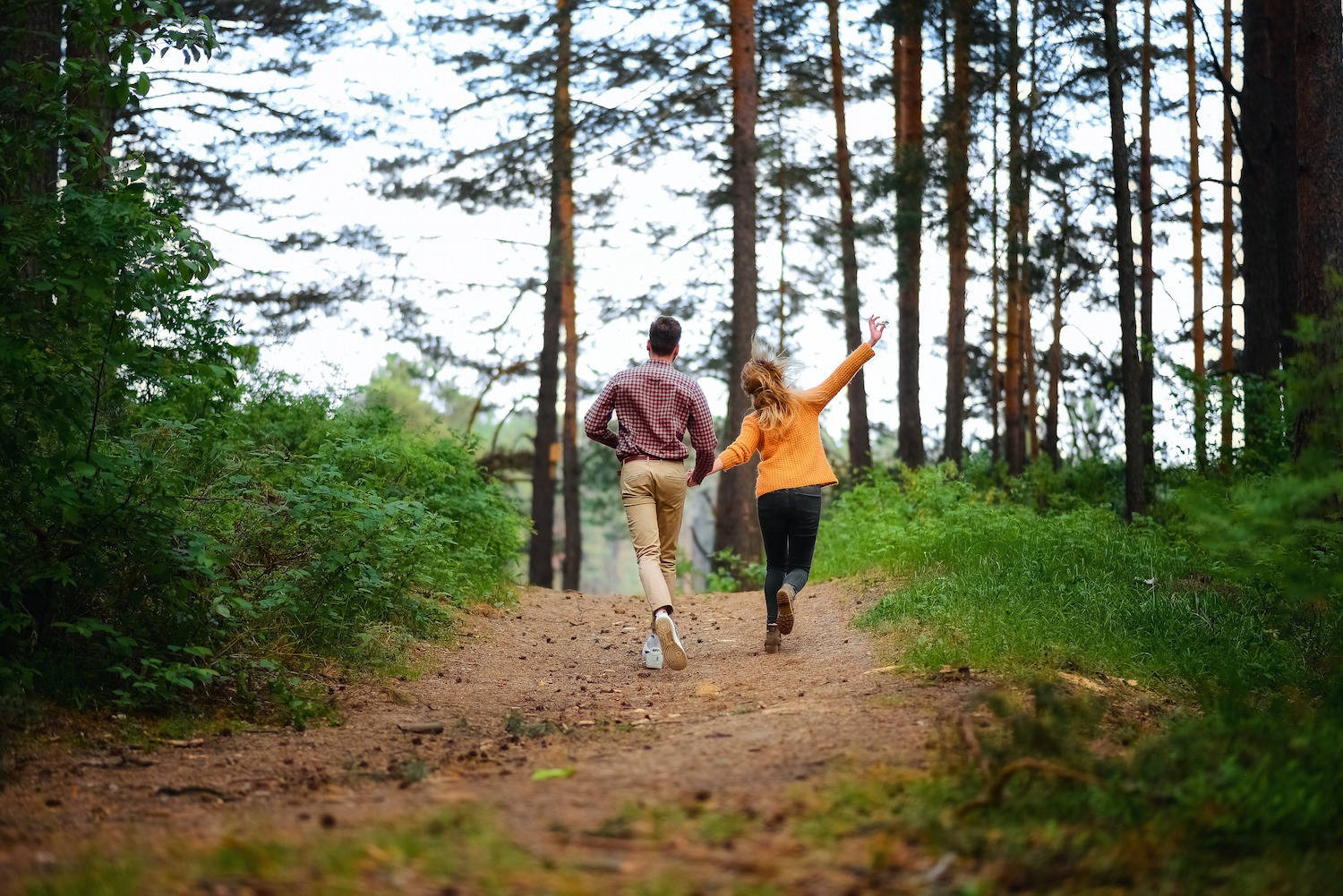 Couple skipping through a forest