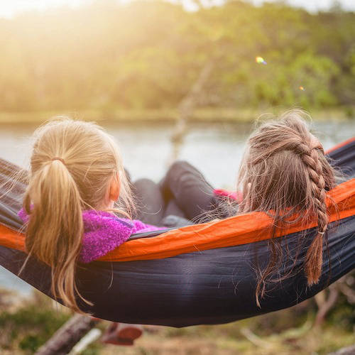 Two young women on a hammock overlooking a lake