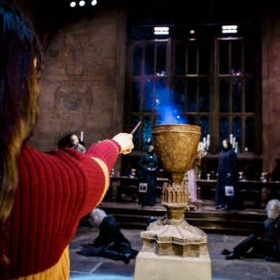 Person holding a wand casting a spell