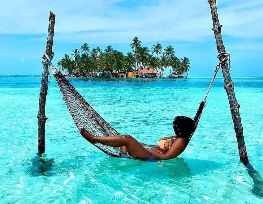 Woman on hammock above blue sea in The Maldives