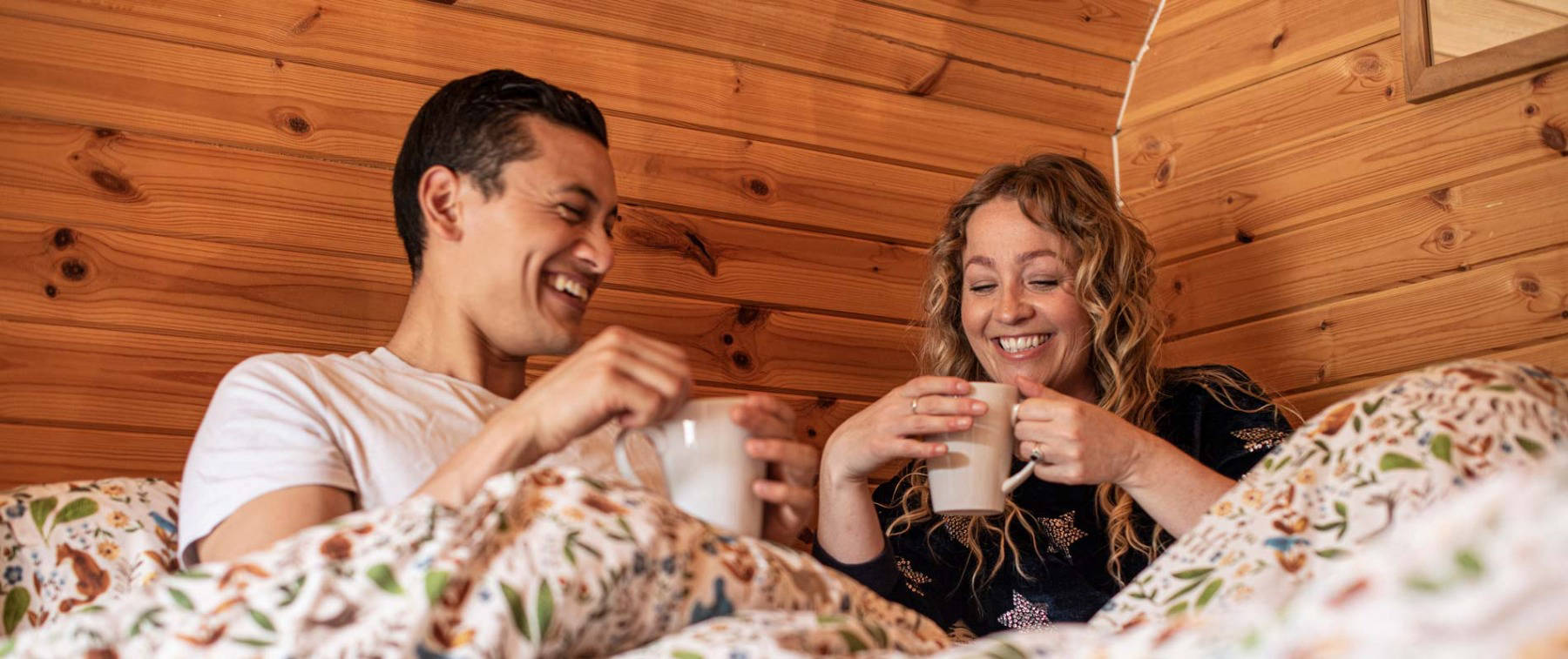 Couple drinking from mugs in cabin