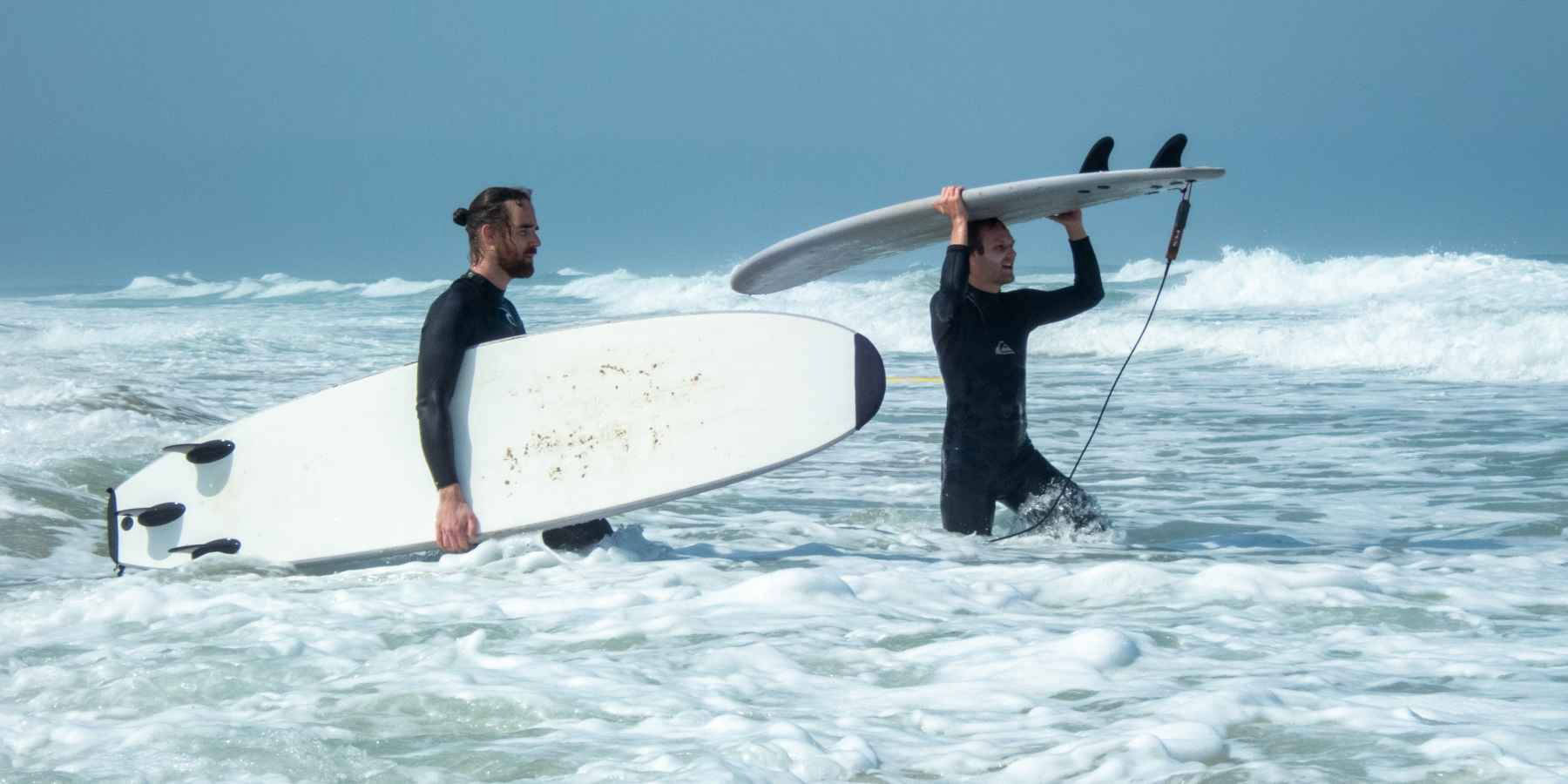 men carrying surf boards