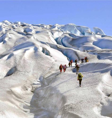 people hiking glacier in greenland