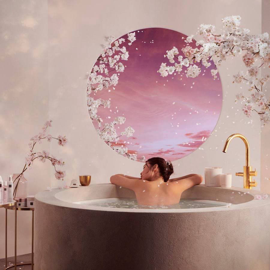 Woman relaxing in a spa bath surrounded by cherry blossom