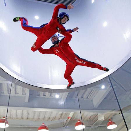 Two people in an indoor skydiving wind tunnel