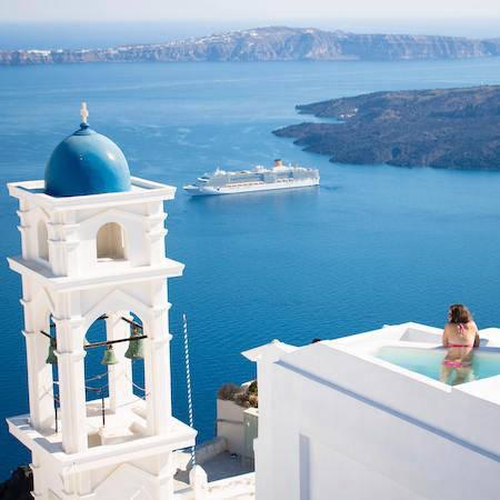 Woman in pool overlooking Santorini