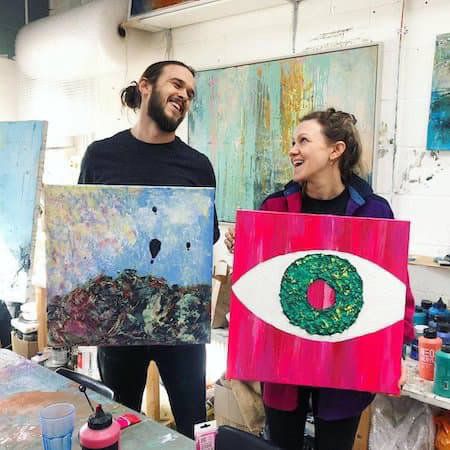 Two people holding their abstract artwork