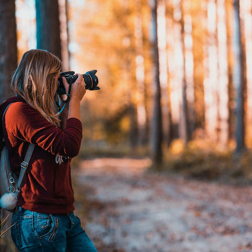 Woman taking a photo in the forest using a DSLR