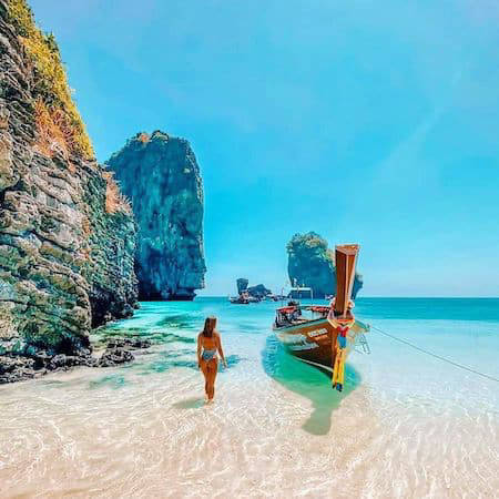 Woman with boat on blue sea in Thailand