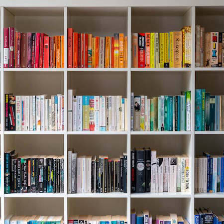 Bookshelves with books arranged by colour