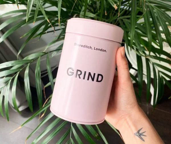 Person holding a Grind coffee tin