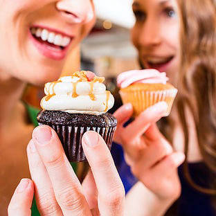 Two people eating decorated cupcakes