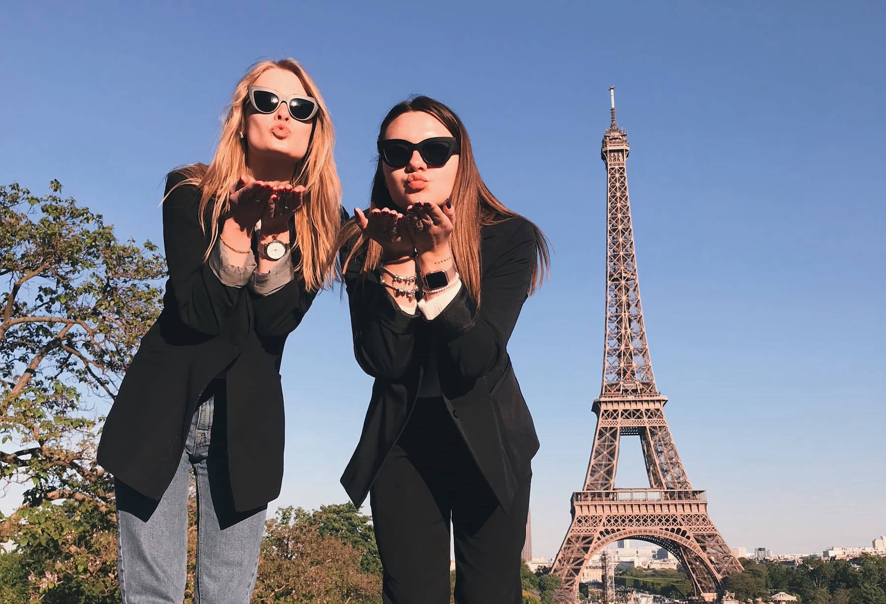 Two women stood in front of Eiffel Tower blowing kisses