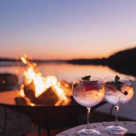 Drinks at a bonfire at a lake