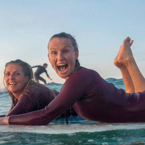 People on surf boards with friends