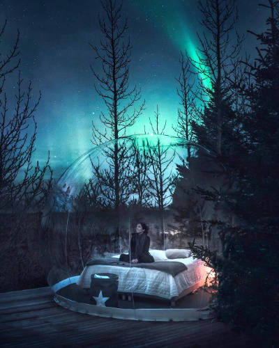 Woman in bubble dome under northern lights