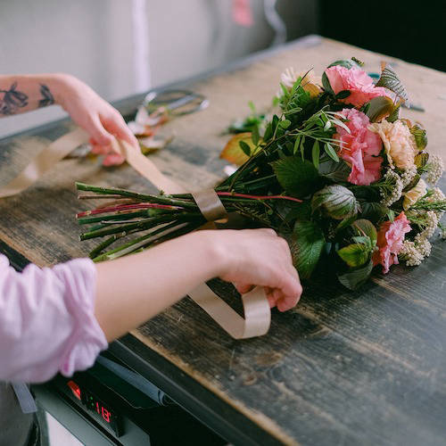 Floral bouquet being hand-tied