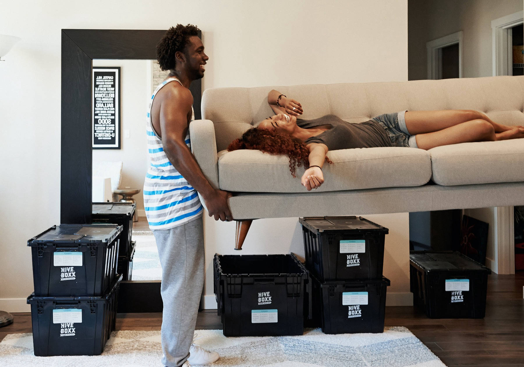 Couple moving house with boxes and sofa