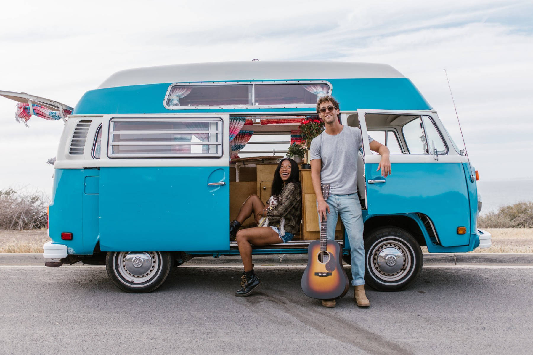 Man and woman with a blue VW Campervan on a roadtrip