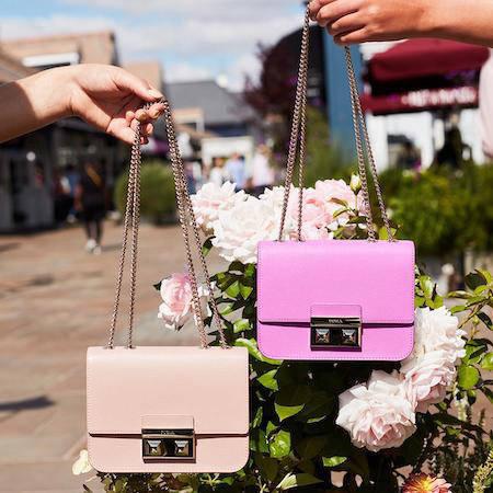Pink handbags in front of flowers