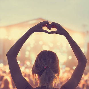 Woman doing a heart with hands at a concert