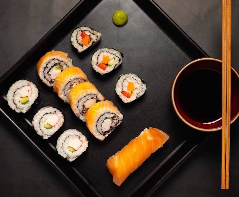 Sushi on a black serving plate with a bowl of soy sauce