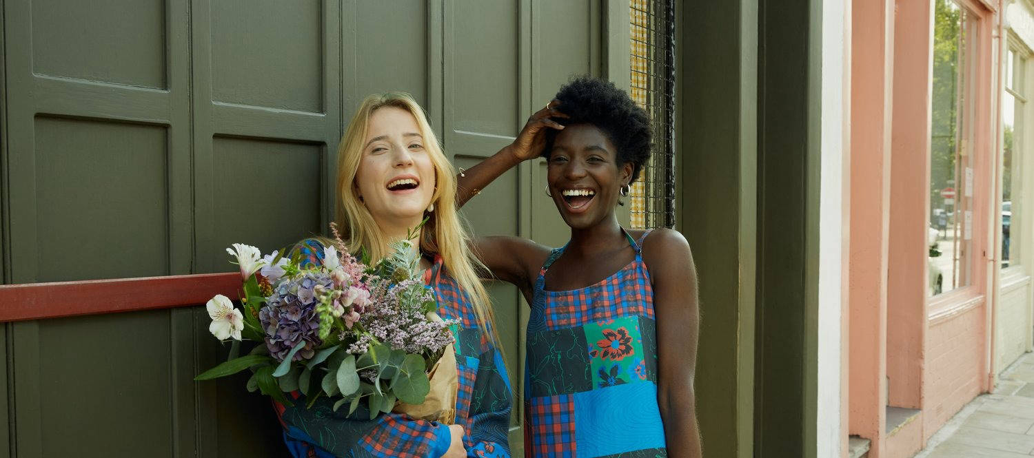 Two women laughing and holding flowers