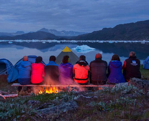 friends with fire overlooking lake in greenland
