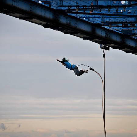 Person bungee jumping off platform