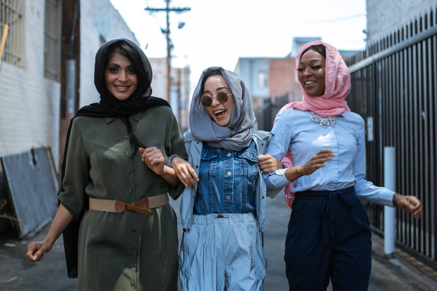 Three women laughing whilst walking down a street