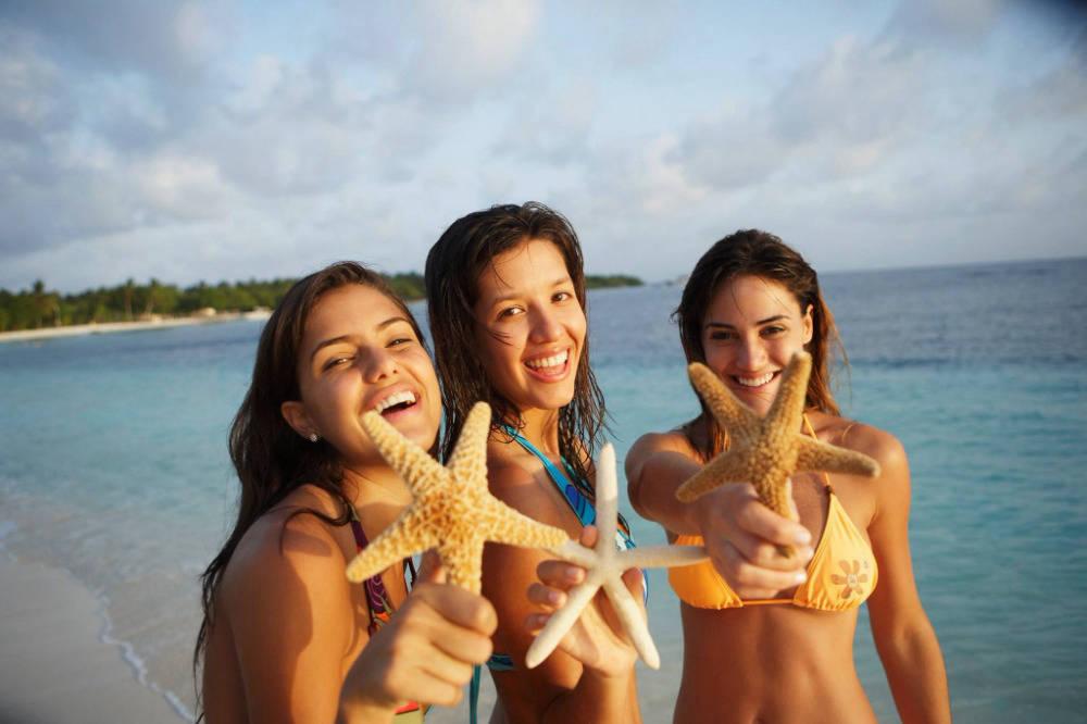 Three women holding starfish on the beach in Punta Cana