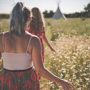 People walking through sunlit field