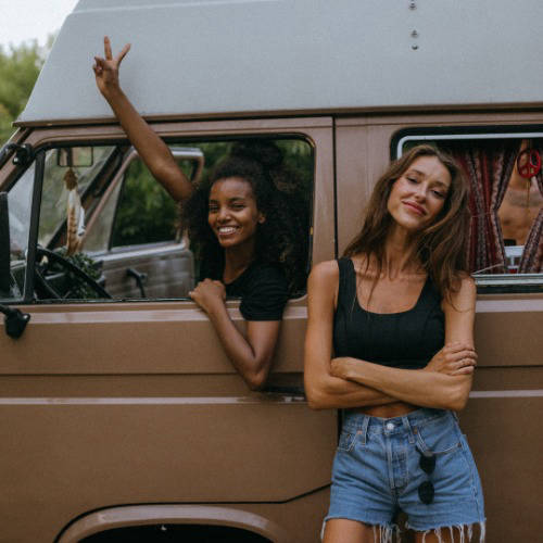 Two women with a brown VW Campervan