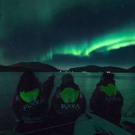 Three people watching the Northern Lights