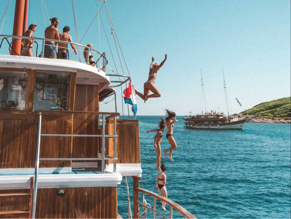 People jumping off a yacht into blue waters