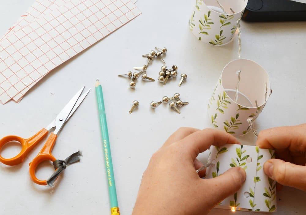Person making fairy lights out of decorated paper