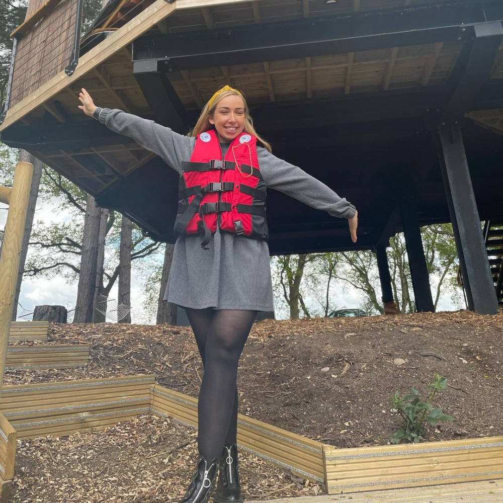 Woman in life jacket in front of tree house