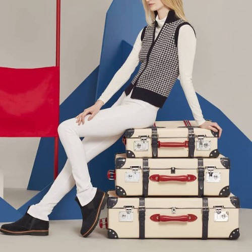 Woman on a pile of luxury suitcases