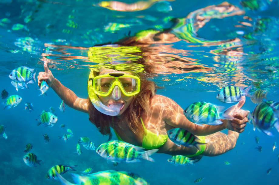 Woman snorkling with fish