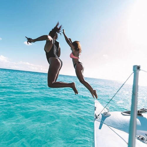 Women on a yacht jumping into the sea