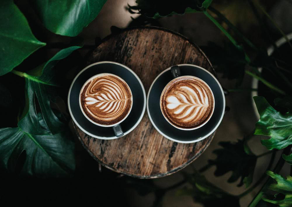 Two coffee cups with coffee art