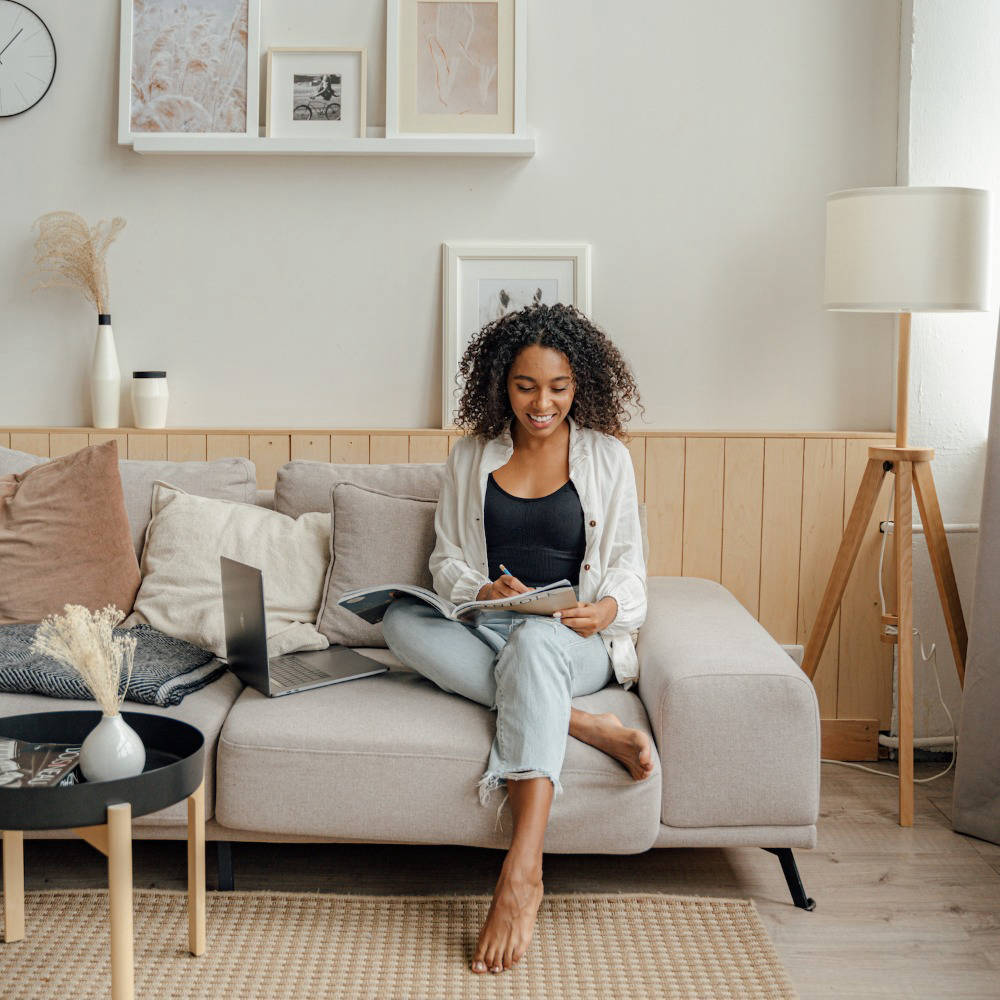 Woman sat on sofa studying or working